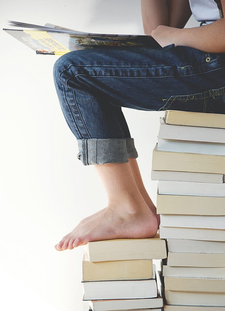 Person reading while sitting on a stack of books.